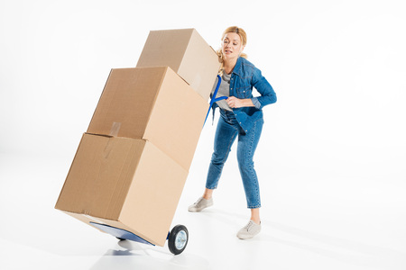 Young woman holding trolley cart loaded with boxes isolated on white Reklamní fotografie
