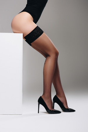 Woman wearing black stockings and heel shoes posing on white box Stock Photo