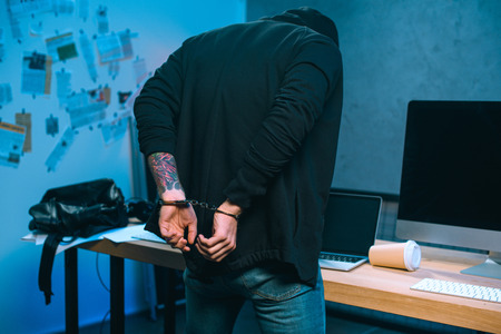 rear view of handcuffed hacker in front of his work desk