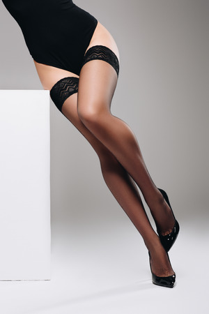 Woman posing in black stockings by white box
