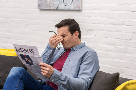 tired adult man rubbing eyes while reading newspaper Banco de Imagens