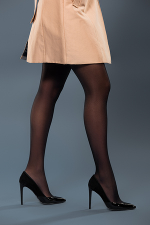 Legs of woman wearing black pantyhose and beige trench on dark background