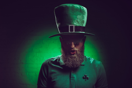 portrait of bearded young man in green irish hat and funny eyeglasses Stock Photo