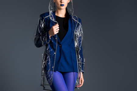Woman posing in blue jacket and transparent raincoat isolated on dark background
