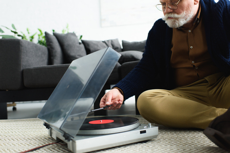 cropped shot of senior man in eyeglasses listening music with vinyl record and turntable at home Archivio Fotografico
