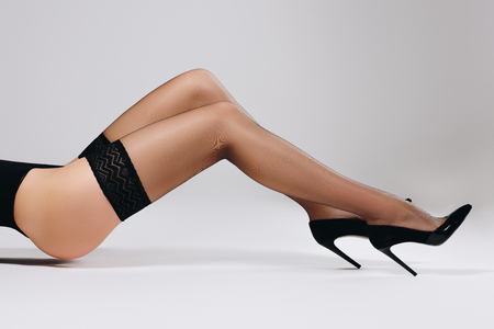 Female legs in black stockings and heel shoes on white background