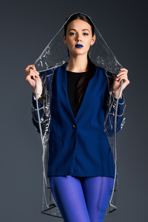 Attractive woman in blue jacket and transparent raincoat isolated on dark background