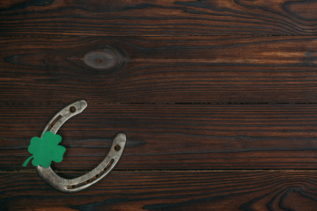 top view of horseshoe and green shamrock on wooden table