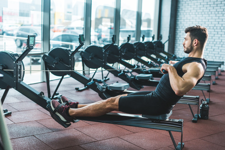 Side view of sportsman doing exercise on rowing machine in sports center 写真素材