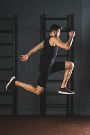 Zijaanzicht van jonge springende sportman in gym