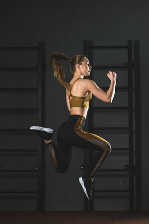 Side view of jumping sportswoman doing cardio exercise in gym Banque d'images
