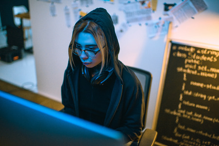 high angle view of female hacker developing malware under blue light