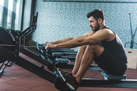 Vista lateral del deportista haciendo ejercicio en la máquina de remo en el centro deportivo