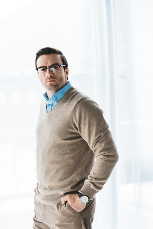 Confident man wearing casual clothes and glasses standing by window