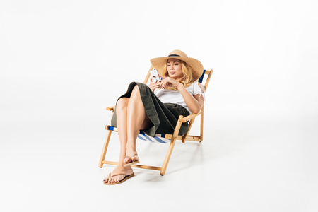 Blonde woman using smartphone and resting in deck chair on white background