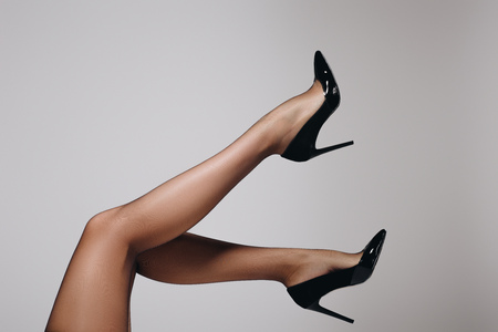 Female legs in black stockings and heel shoes isolated on grey background Foto de archivo