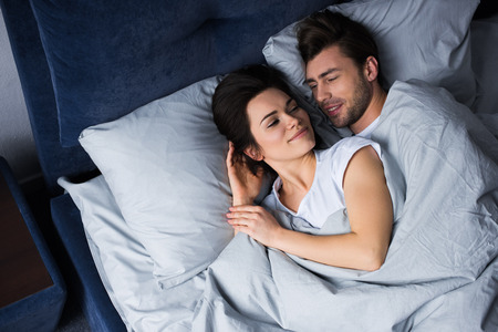 Romantic couple lying in bed in their room Standard-Bild - 112317315