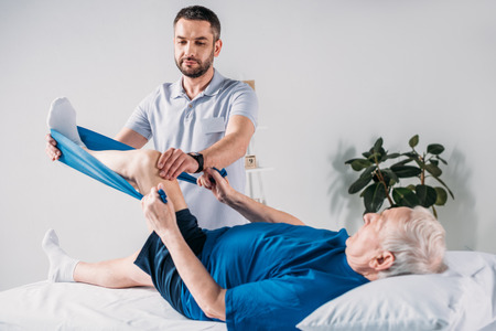 rehabilitation therapist assisting senior man exercising with rubber tape on massage table