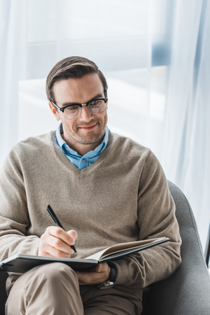 Male psychologist in glasses writing down patient complaints