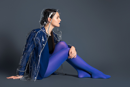 Stylish woman in blue tights and transparent raincoat sitting on dark background Zdjęcie Seryjne - 112317320