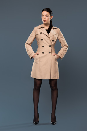 Young woman in black tights and beige trench on dark background