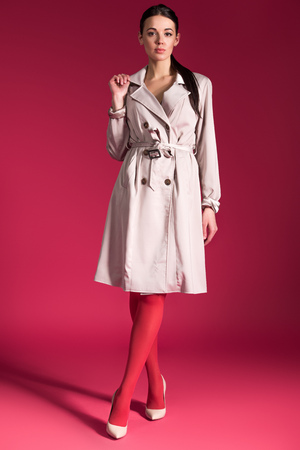 Slim woman in red pantyhose and beige trench on red background