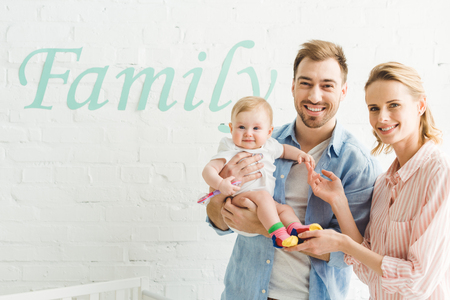 Young caucasian family with infant daughter, lettering family on wall Banco de Imagens