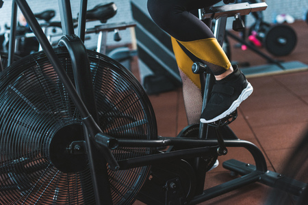 Cropped image of sportswoman doing workout on exercise bike in sports center Stockfoto