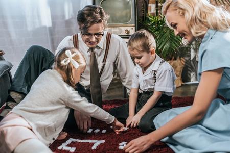 lächelnde altmodische Familie, die zu Hause zusammen Domino spielt