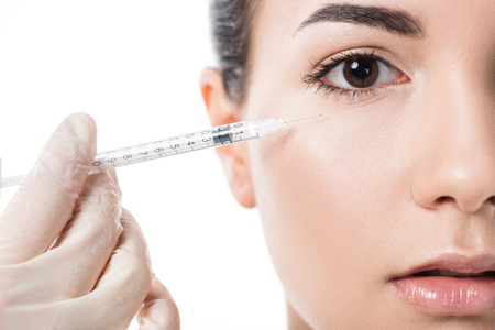 cropped image of cosmetologist making beauty injection to girl with clean skin isolated on white