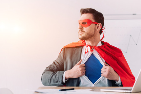 serious super businessman in mask and cape showing blue shirt in office