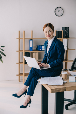 smiling businesswoman with laptop sitting on table in office Stock fotó
