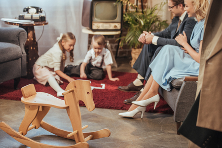 wooden rocking horse and happy 50s style family spending time together at home Stock Photo