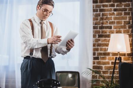 1950s style man in eyeglasses using digital tablet at home