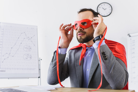 super businessman in cape looking through red mask in office Stock Photo
