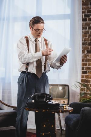 retro styled man in eyeglasses using digital tablet at home 版權商用圖片