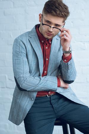 Bearded young man wearing stylish glasses by brick wall