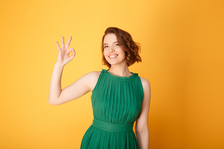 portrait of pretty smiling woman showing ok sign isolated on orange