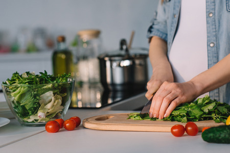 cropped image of attractive pregnant woman cutting vegetables for salad at kitchen