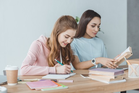 multiethnic girls studying together and writing in copybook and reading book at table