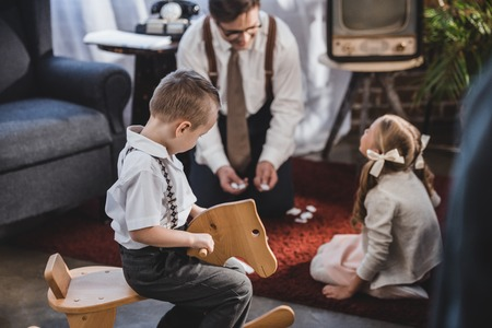 little boy sitting on rocking horse while father with daughter playing dominoes behind, 50s style family