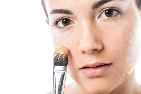 beautiful girl applying honey mask on face with brush isolated on white 免版税图像