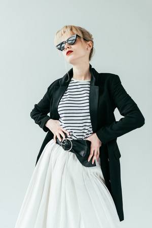 Attractive young woman wearing retro sunglasses isolated on grey