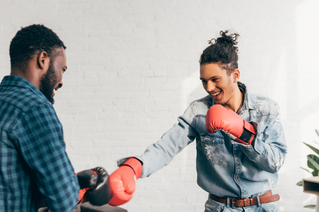 young smiling multiethnic male friends doing sparring in boxing gloves