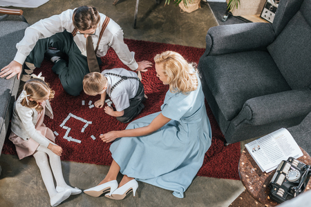 overhead view of 1950s family with two kids playing dominoes together at home