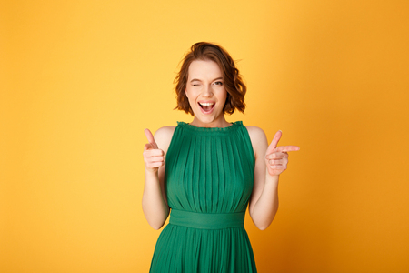 portrait of winking woman pointing at camera isolated on orange