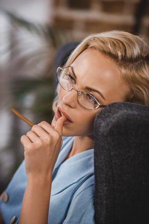 beautiful blonde woman in eyeglasses holding cigarette and looking away, fifties style 版權商用圖片