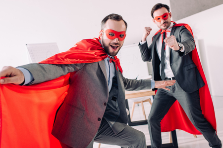 handsome super businessmen in masks and capes having fun in office
