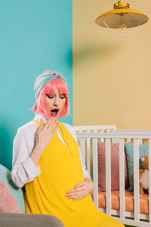 shocked retro styled pregnant woman with pink hair sitting near baby cot in child room