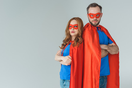 super couple in masks and cloaks standing with crossed arms and looking at camera isolated on grey